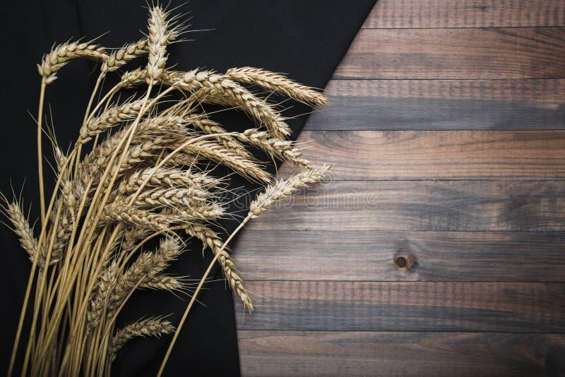 Natura morta agricola delle orecchie del grano sui popolare di tessuto nero immagine stock