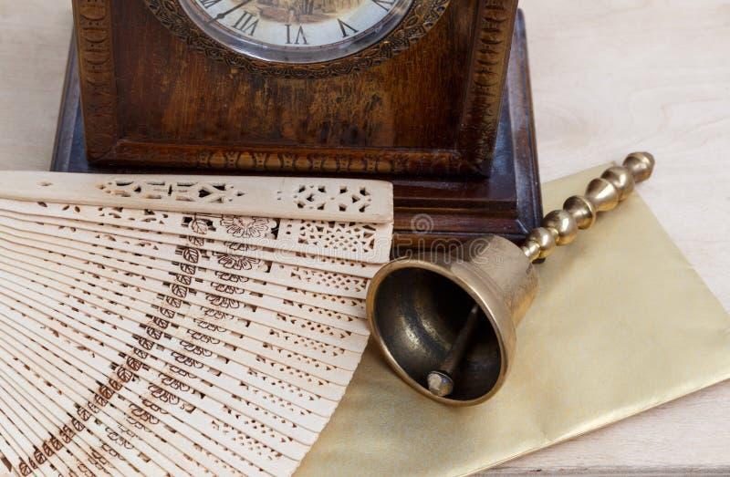 Natura morta, campana d'ottone, orologio antico e fan di legno scolpito immagine stock libera da diritti