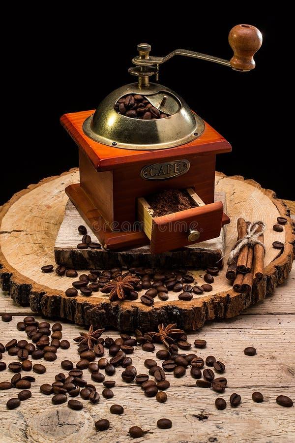 Natura morta con i chicchi di caffè ed il vecchio mulino di caffè fotografie stock