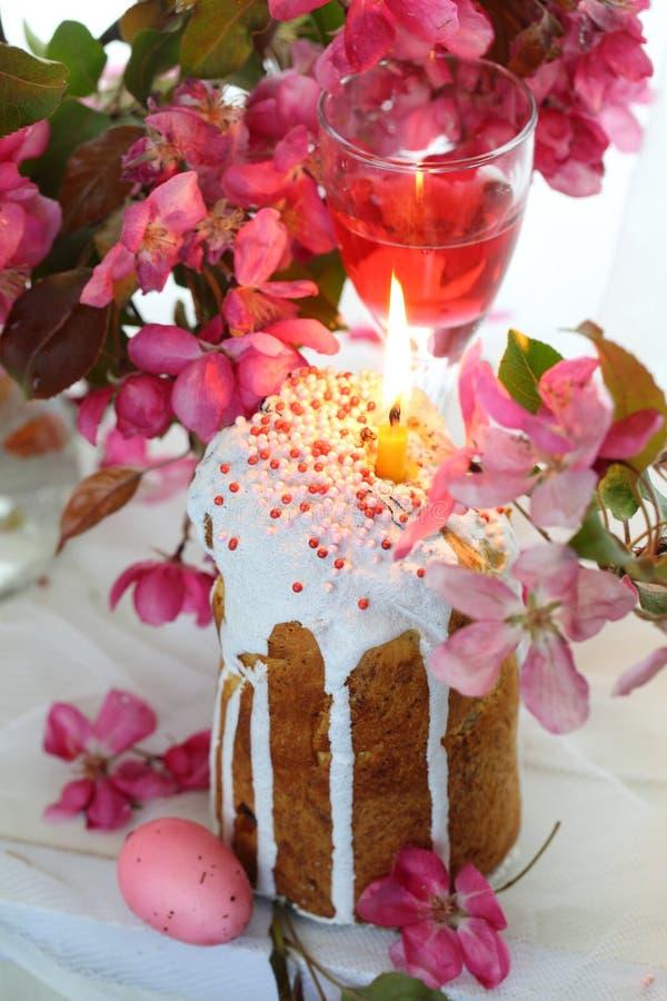 Natura morta con i dolci di Pasqua, le uova dipinte, il vino ed i fiori della mela di paradiso immagini stock