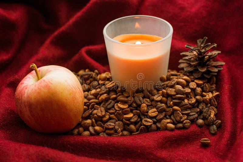 Natura morta con i grani di caffè, di una mela, di una candela bruciante e di un cono fotografie stock libere da diritti