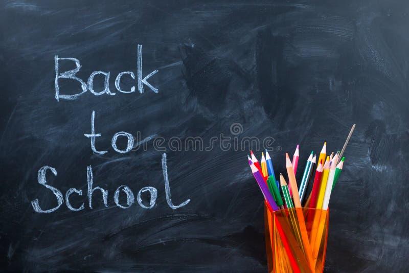 Natura morta con i libri, le matite e la mela di scuola contro il blackboa immagine stock