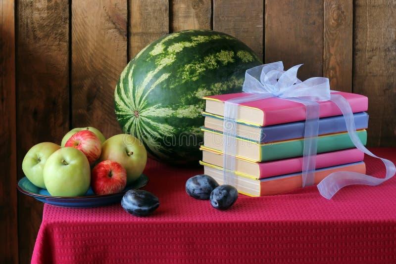 Natura morta con i libri, le prugne, un'anguria e le mele fotografie stock libere da diritti