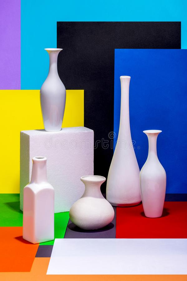 Natura morta con i vasi bianchi su un fondo astratto di colore fotografia stock libera da diritti