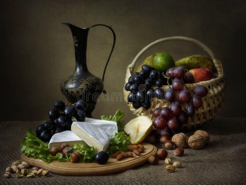 Natura morta con il canestro dei frutti e del formaggio sulla tavola fotografia stock