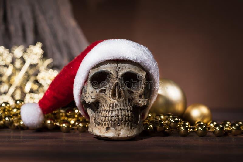 Natura morta con il cranio del Babbo Natale e l'ornamento di natale dell'oro immagine stock libera da diritti