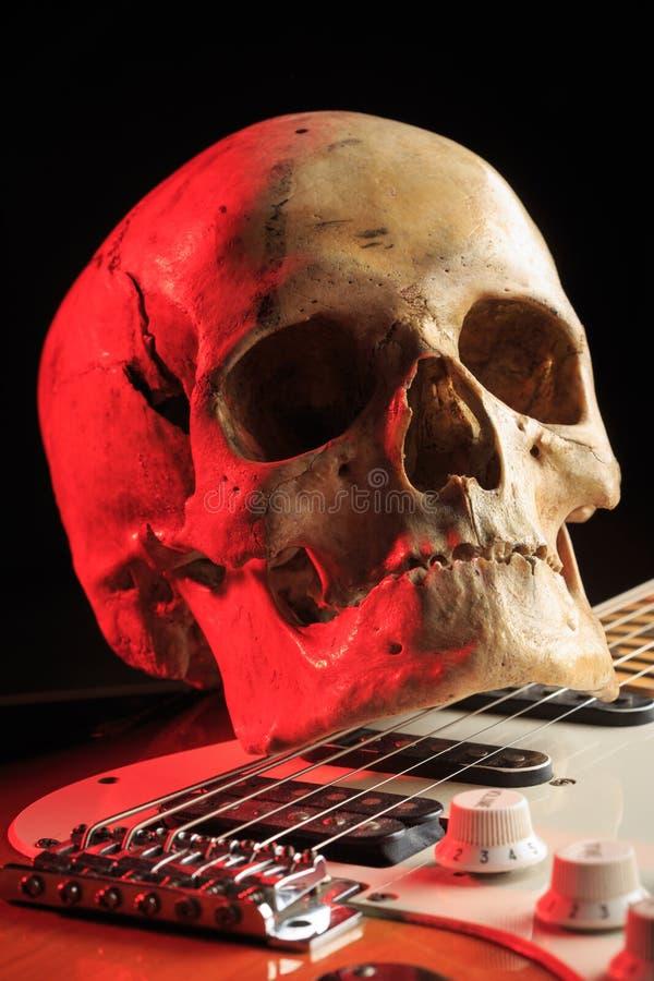 Natura morta con il cranio e la chitarra elettrica fotografia stock libera da diritti