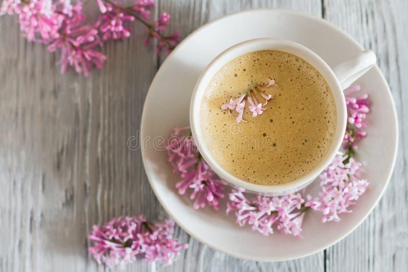 Natura morta con il fiore del lillà della molla e della tazza di caffè immagini stock