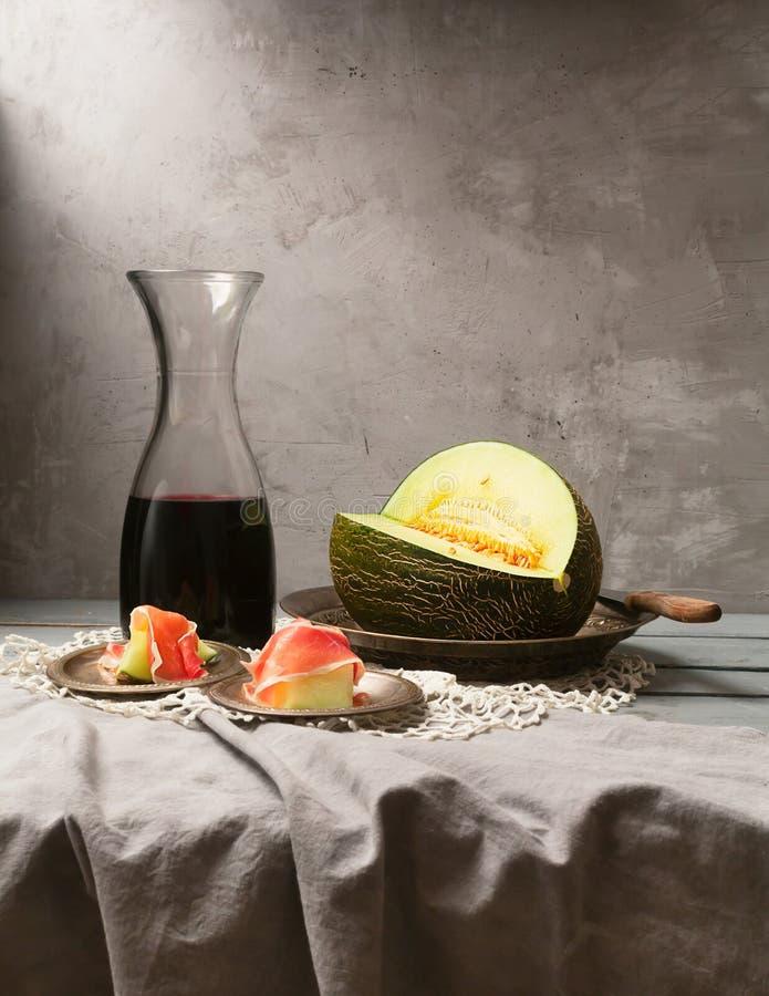 Natura morta con il melone fresco, il jamon ed il vino rosso sulla tavola fotografia stock libera da diritti