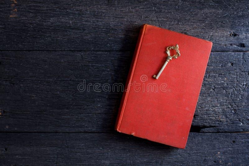 Natura morta con il vecchio libro e chiave su di legno immagini stock libere da diritti