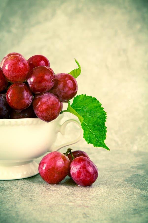 Natura morta con l'uva rossa in tazza d'annata bianca fotografie stock libere da diritti