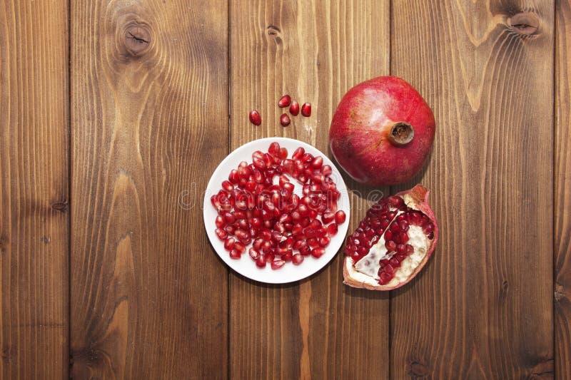 Natura morta con la frutta del melograno su fondo di legno fotografia stock