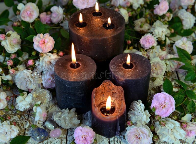 Natura morta con le candele e le rose nere sulla tavola verde della strega immagine stock