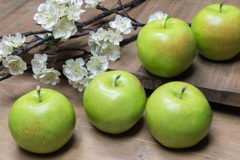 Natura morta con le mele verdi e fiore su fondo di legno immagine stock
