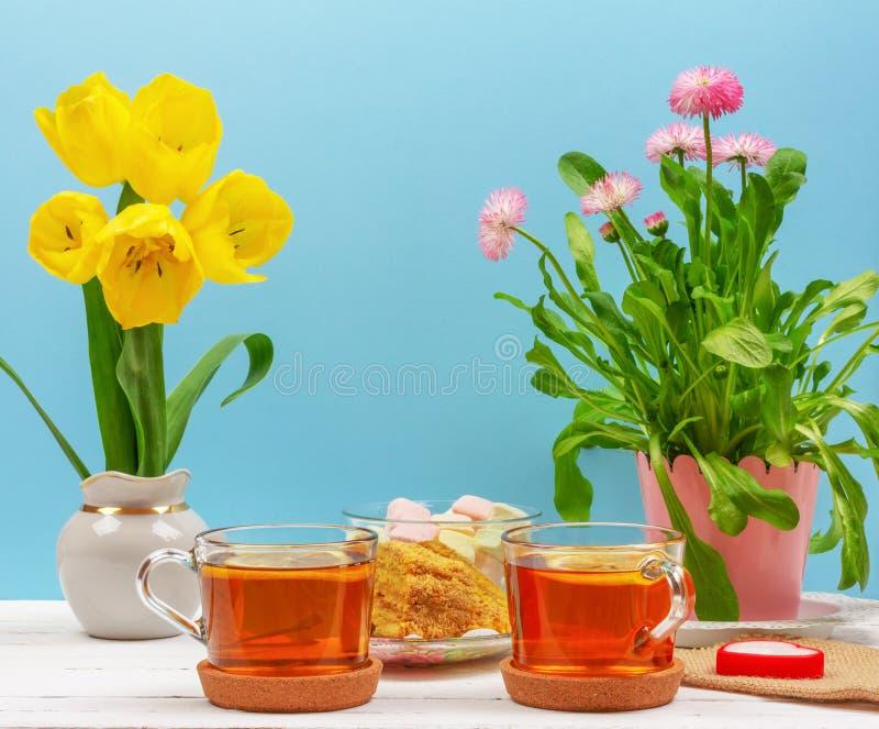Natura morta con le tazze di tè, pezzi di dolce, mazzo dei fiori rosa in un vaso rosa, caramella gommosa e molle e candela in for fotografie stock libere da diritti