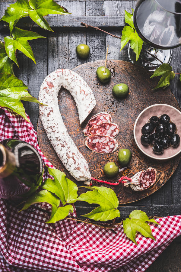 Natura morta con tipico dei antipasti italiani: salame, varie olive, foglie dell'uva e vino rosso sul tavolo da cucina di legno s fotografie stock libere da diritti