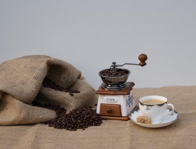 Natura morta con un macinacaffè nostalgico e una tazza di caffè con caffè appena fatto fotografia stock libera da diritti