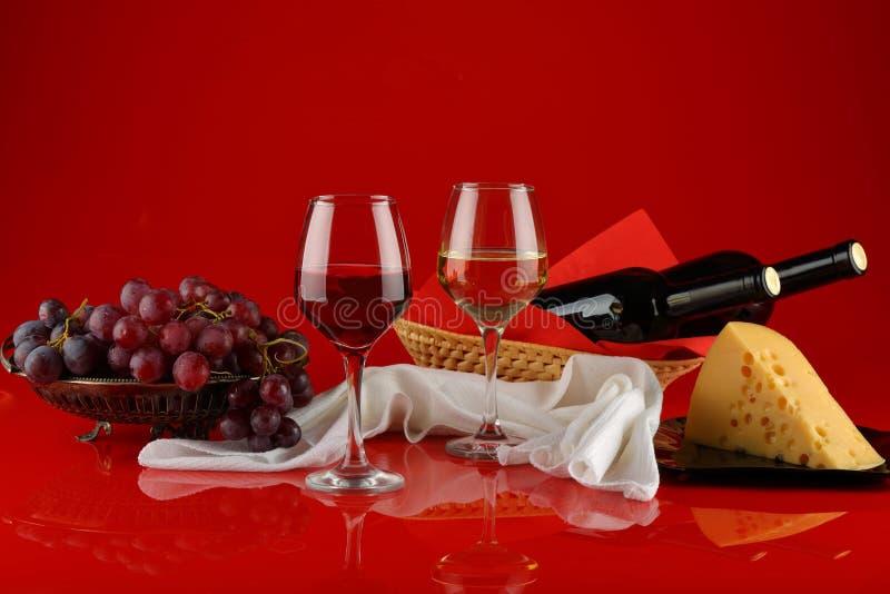 Natura morta con vino, formaggio e l'uva su un fondo rosso immagine stock libera da diritti