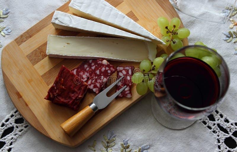 Natura morta con vino, formaggio a pasta molle fotografie stock