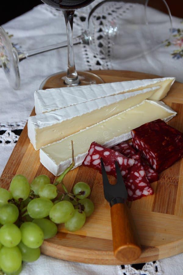 Natura morta con vino, formaggio a pasta molle fotografia stock