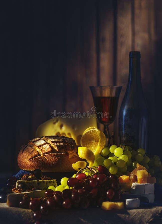 Natura morta con vino, l'uva, il pane e le varie specie di formaggio fotografia stock libera da diritti