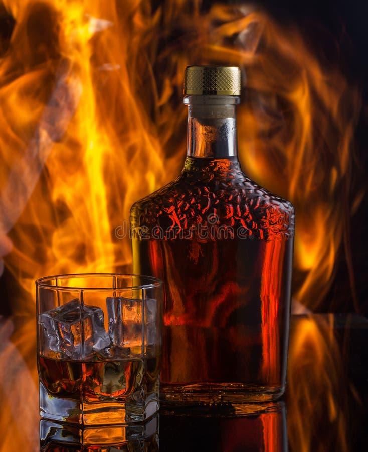 Natura morta con whiskey sui precedenti di fuoco fotografie stock
