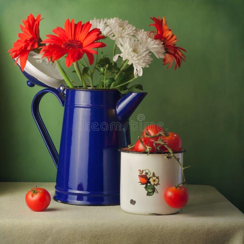 Natura morta d'annata con i fiori ed i pomodori ciliegia fotografie stock
