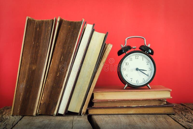 Natura morta d'annata della pila di vecchi libri con la sveglia su rosso immagine stock libera da diritti