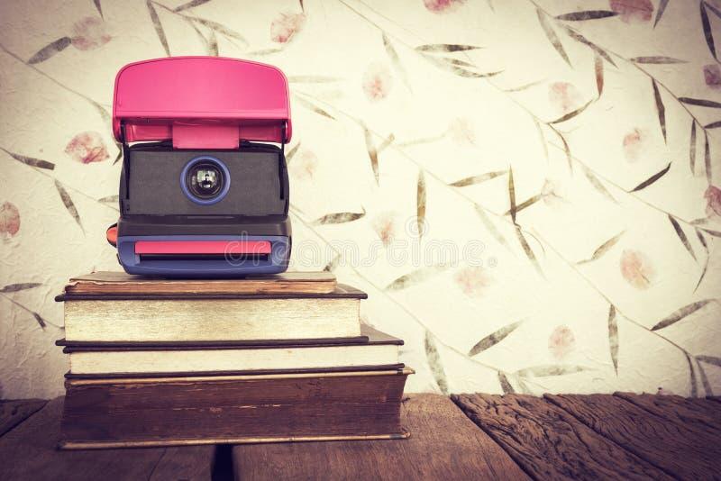 Natura morta d'annata della pila di vecchi libri con la vecchia macchina fotografica sullo swee immagine stock