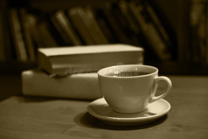 Natura morta d'annata, tazza con tè e libri, seppia fotografie stock