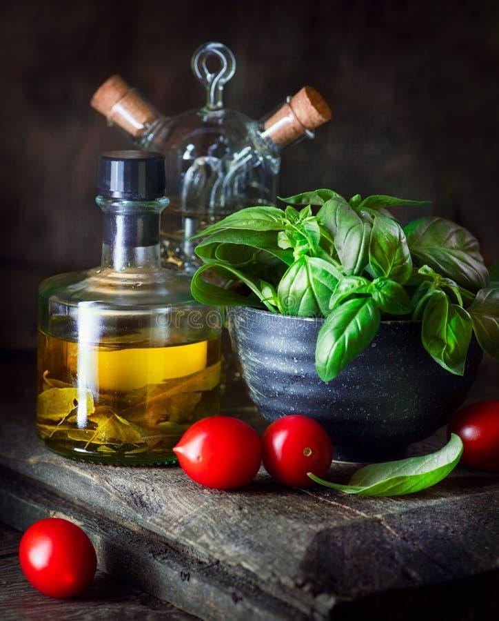 Natura morta degli ingredienti alimentari Olio d'oliva, pomodori ciliegia, basilico fresco immagini stock libere da diritti