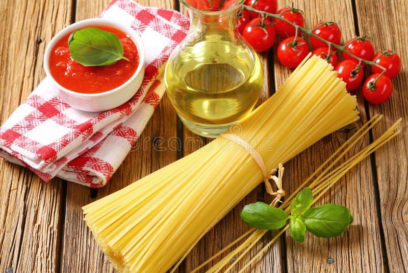 Natura morta degli spaghetti, del concentrato di pomodoro e dell'olio d'oliva secchi fotografia stock libera da diritti