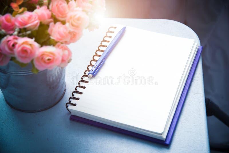 Natura morta del taccuino e della penna in bianco con il fiore filte d'annata fotografia stock