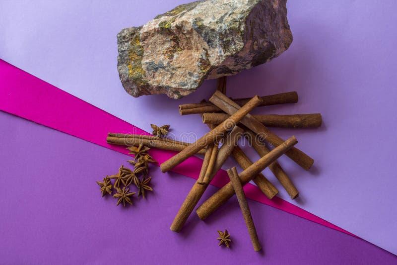 Natura morta della pietra, dei bastoni di cannella e delle stelle dell'anice trovantesi sul fondo colorato fotografia stock libera da diritti