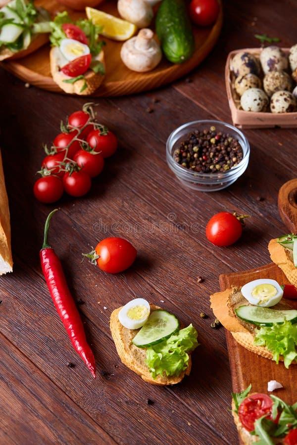 Natura morta della prima colazione con i panini, uova di quaglia, spicies e frutta e verdure fresche, fuoco selettivo immagini stock
