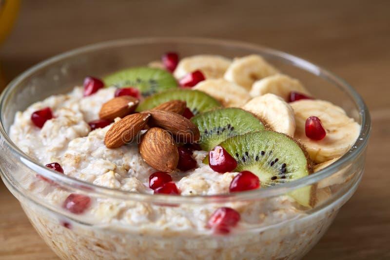 Natura morta della prima colazione con il porridge della farina d'avena ed i frutti, vista superiore, fuoco selettivo, profondità immagini stock libere da diritti