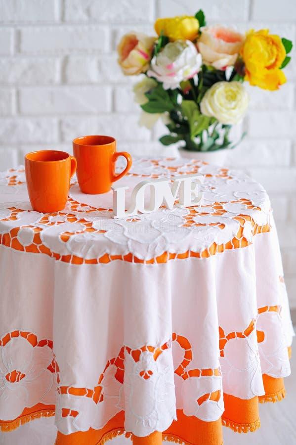 Natura morta della primavera con i fiori e le tazze arancio fotografia stock libera da diritti