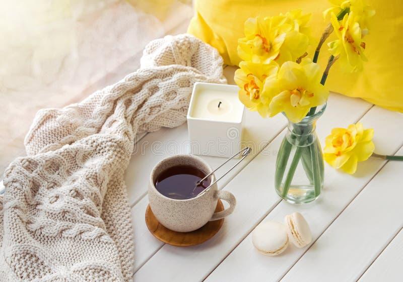 Natura morta della primavera con i fiori gialli, tè e candela, fotografie stock