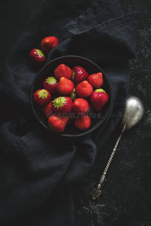 Natura morta delle fragole fresche su fondo concreto nero fotografia stock
