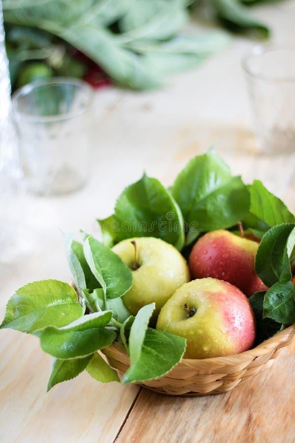 Natura morta delle mele verdi in un canestro sul grande piano della tavola fotografia stock libera da diritti