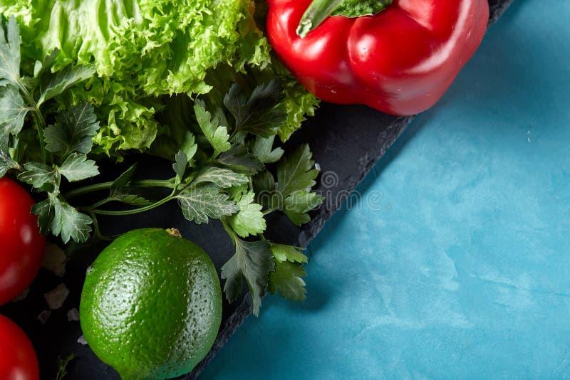 Natura morta delle verdure organiche fresche sul piatto di legno sopra fondo blu, fuoco selettivo, primo piano fotografia stock libera da diritti
