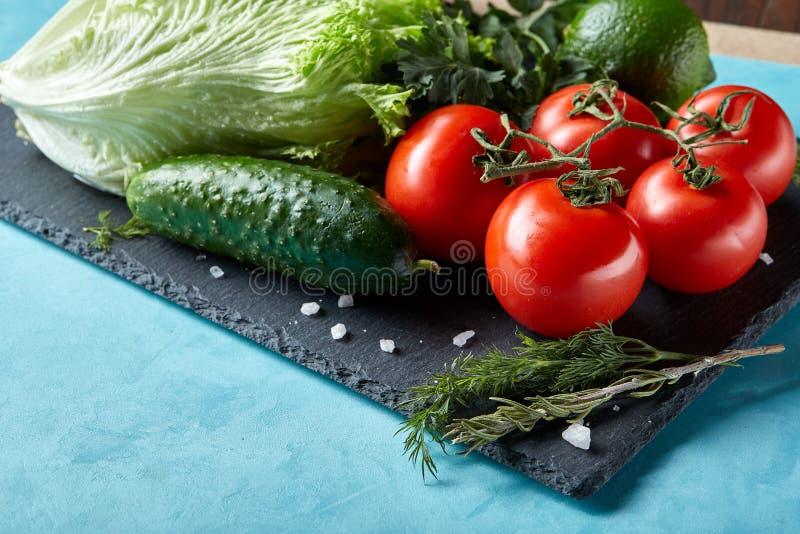 Natura morta delle verdure organiche fresche sul piatto di legno sopra fondo blu, fuoco selettivo, primo piano fotografie stock libere da diritti