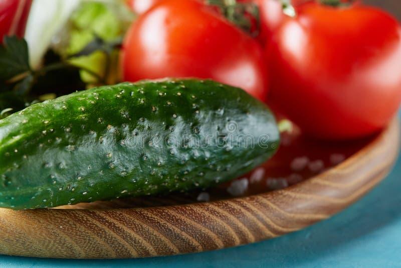 Natura morta delle verdure organiche fresche sul piatto di legno sopra fondo blu, fuoco selettivo, primo piano immagini stock libere da diritti