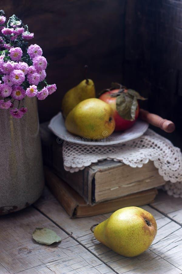 Natura morta di autunno con le pere, la mela, i crisantemi ed i libri Stile rustico immagine stock libera da diritti