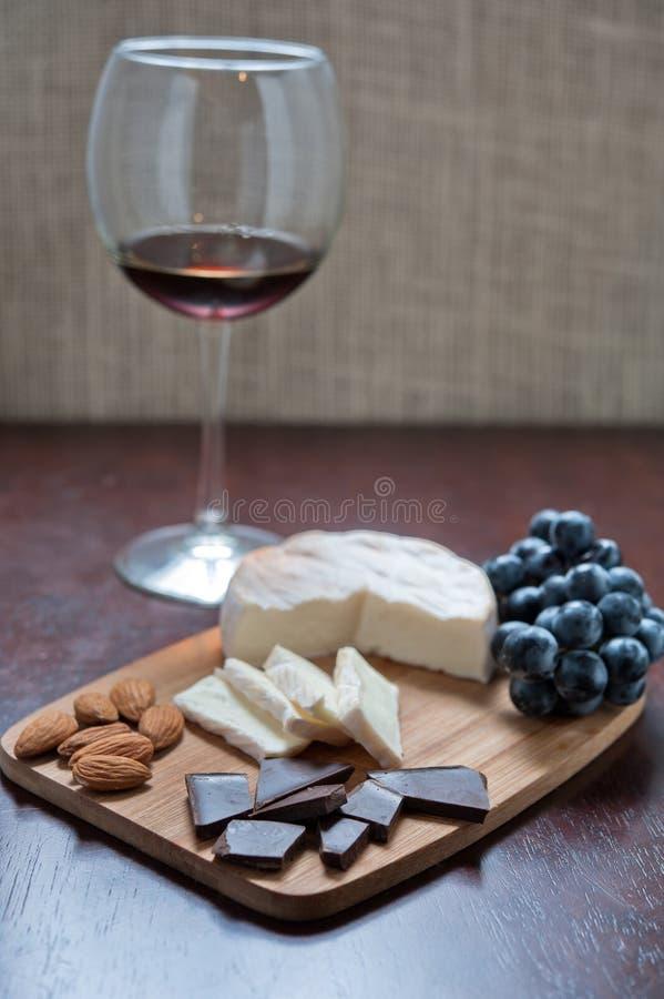 Natura morta di Brie, delle mandorle, del cioccolato, dell'uva e del vino fotografia stock libera da diritti
