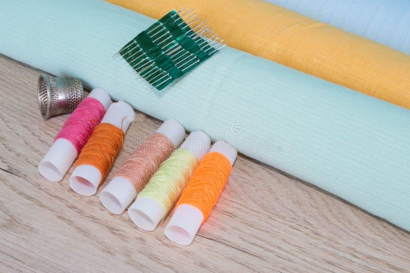 Natura morta di cucito: panno variopinto Il corredo di cucito include i fili dei colori differenti, del ditale e di altri accesso immagine stock libera da diritti