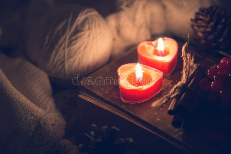 Natura morta di inverno con le bacche di sorbo, il maglione tricottato e le candele dei due rossi su un vecchio libro come simbol fotografie stock