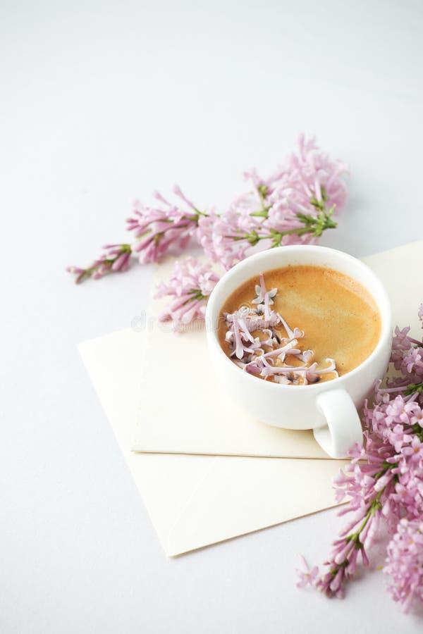 Natura morta di Minimalistic con caffè ed i rami lilla, buste sulla tavola bianca, concetto femminile di mattina, spazio della co immagine stock