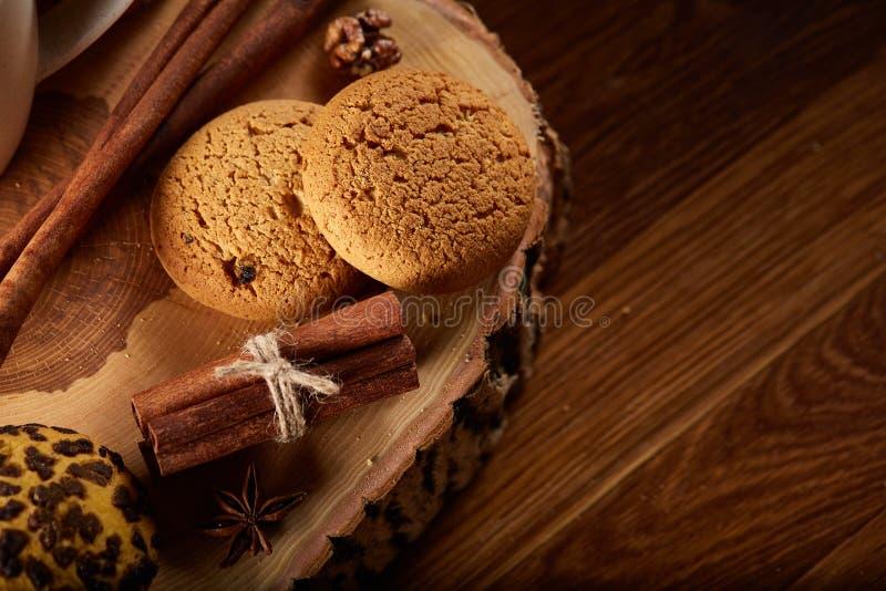 Natura morta di Natale con l'assortimento dei biscotti, della cannella e delle arance secche su un ceppo, primo piano, fuoco sele fotografia stock libera da diritti