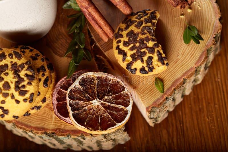 Natura morta di Natale con l'assortimento dei biscotti, della cannella e delle arance secche su un ceppo, primo piano, fuoco sele fotografia stock